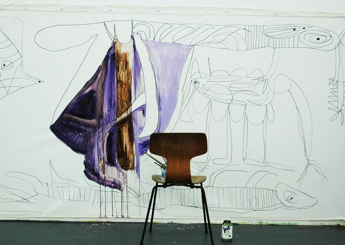 Ein leerer Stuhl vor einer unfertigen Bildskizze.