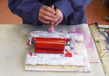 Einfärben der Linolplatte mit der Walze