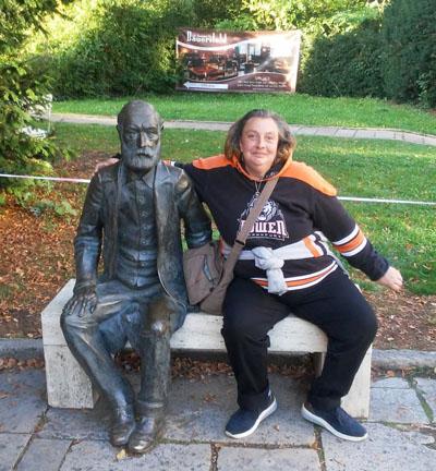 Eine Teilnehmerin der Erfurt-Fahrt auf einer Bank mit einer Bronze-Skulptur.